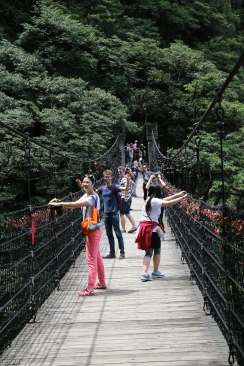 Teachers and staff being led by Anyuan Volunteer Association across a bridge in Wugong Mountain National Park, 2015